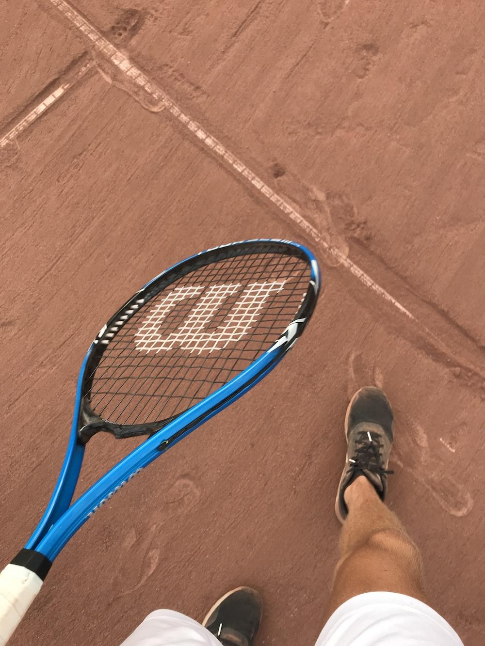 blue and black tennis racket on brown concrete floor