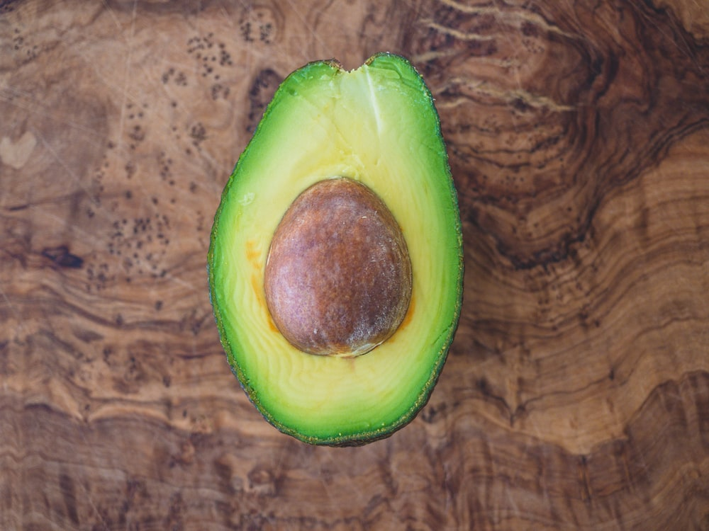 sliced avocado fruit on brown wooden table