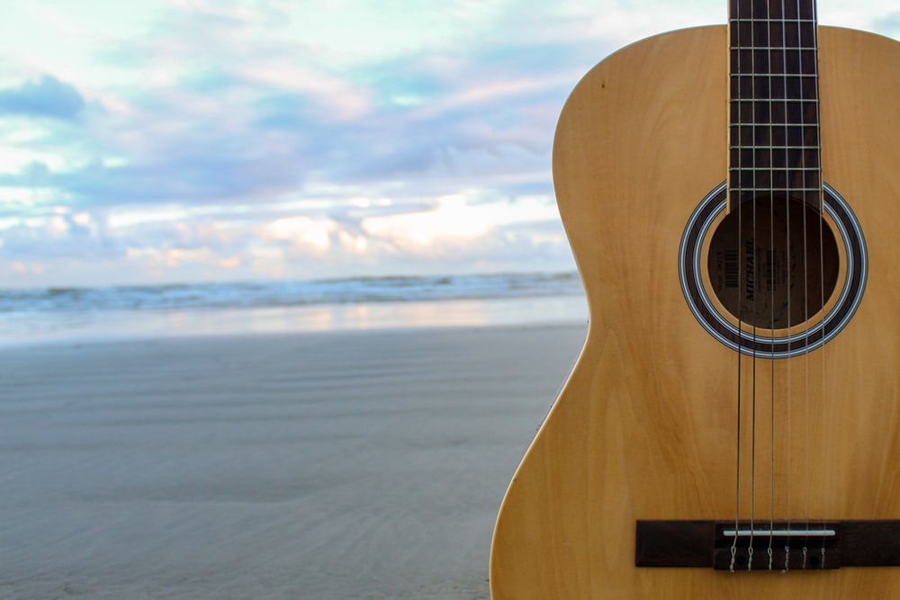 brown acoustic guitar on beach during daytime
