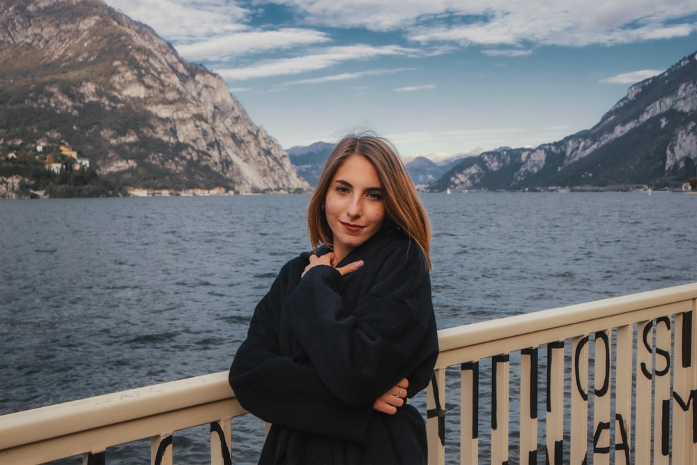 woman in black long sleeve dress standing beside white railings near body of water during daytime