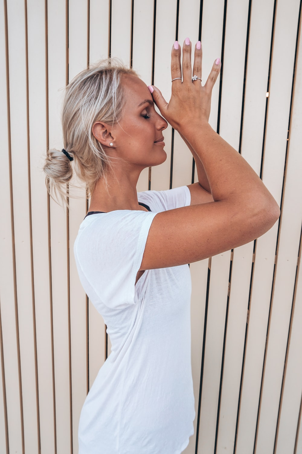 woman in white t-shirt holding her hair