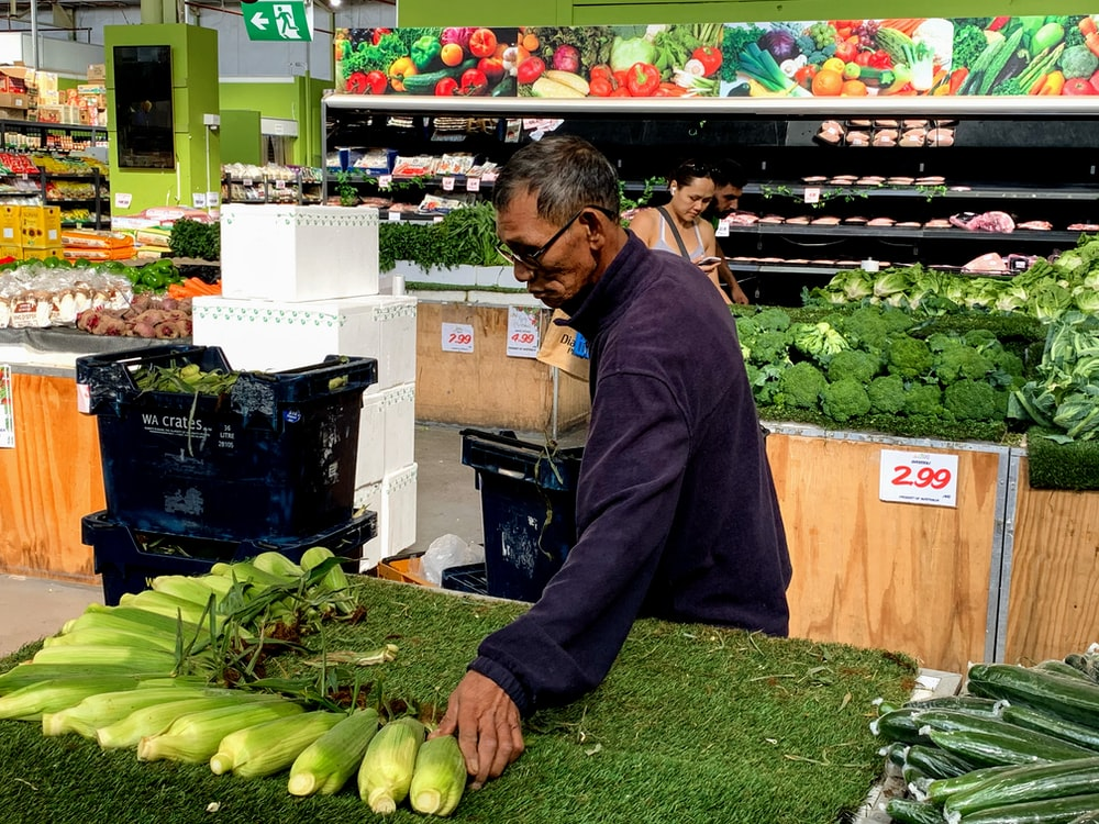 man in black jacket holding green vegetable