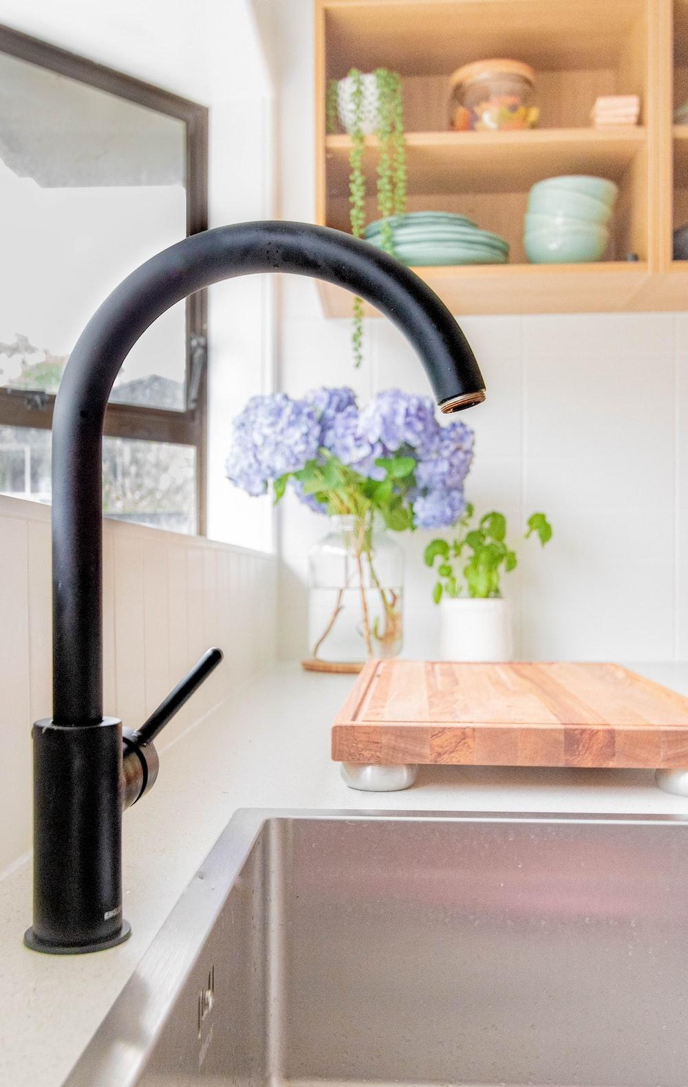 black metal faucet near brown wooden chopping board