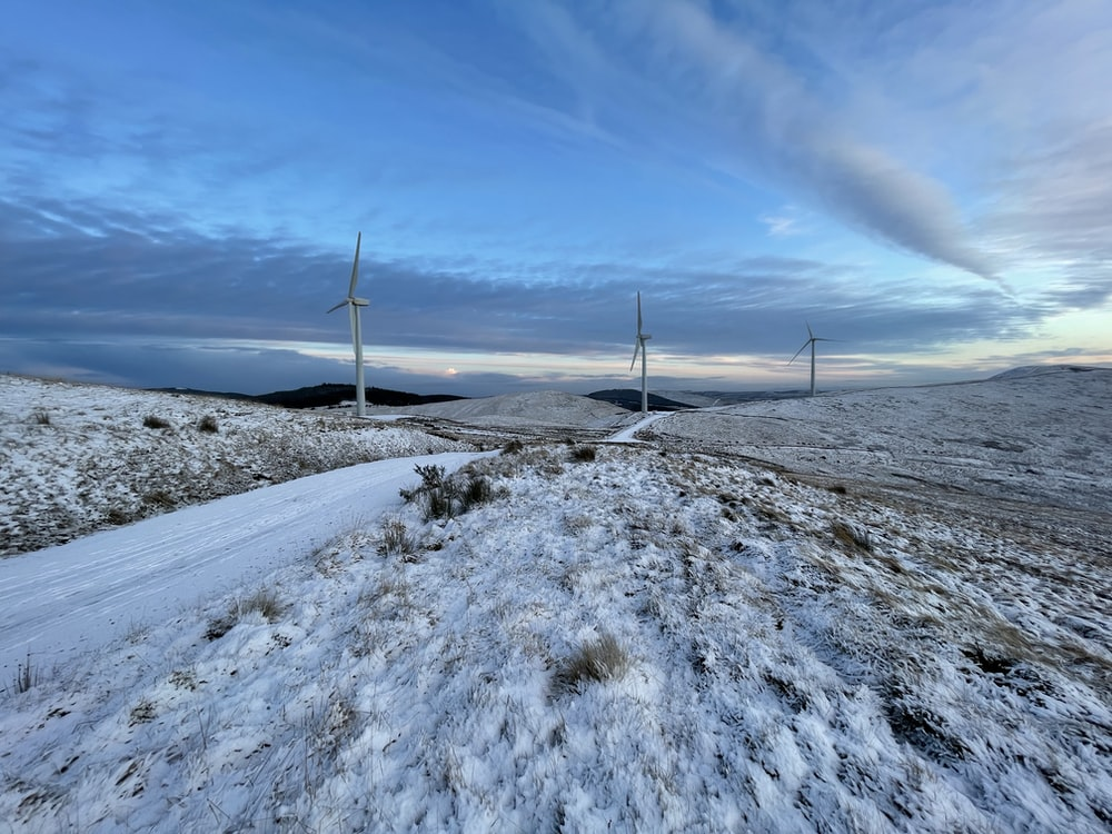 white wind turbines on snow covered ground under blue sky during daytime