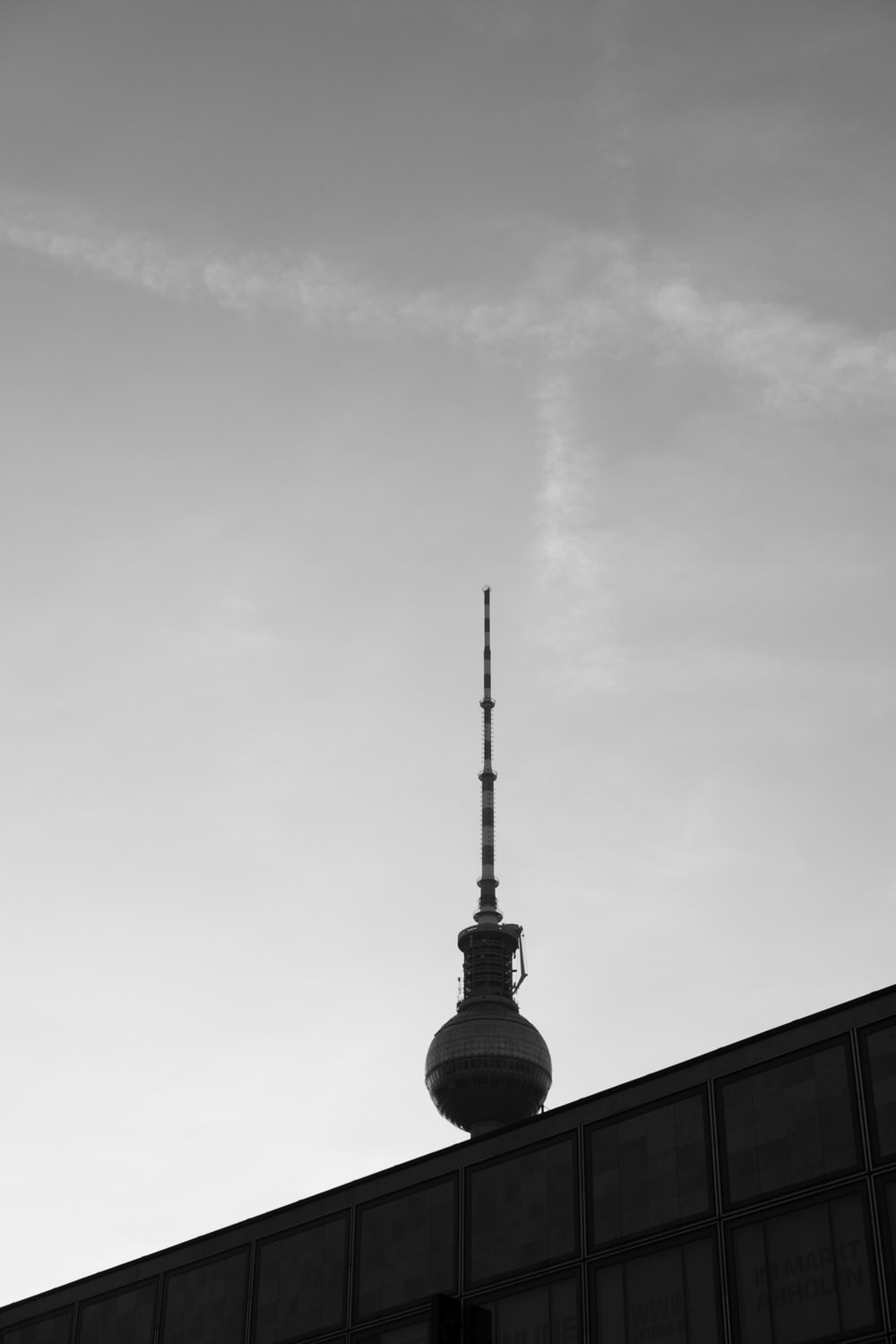 grayscale photo of tower under cloudy sky