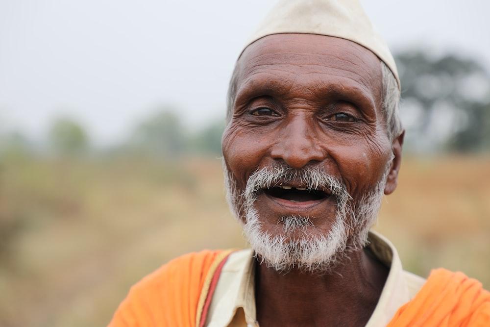 man in orange and white shirt smiling