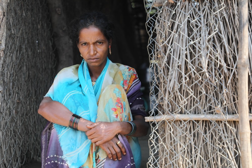 woman in white and green sari holding brown wooden stick