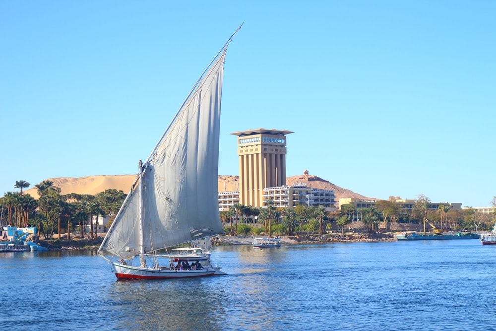 white sail boat on water near city buildings during daytime