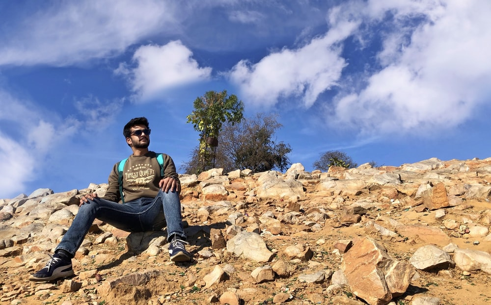 man in green and black jacket sitting on brown rock formation under blue and white sunny
