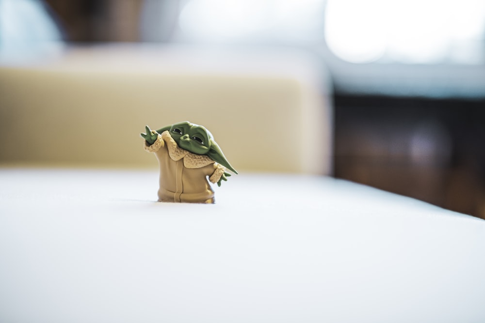 green frog figurine on white table