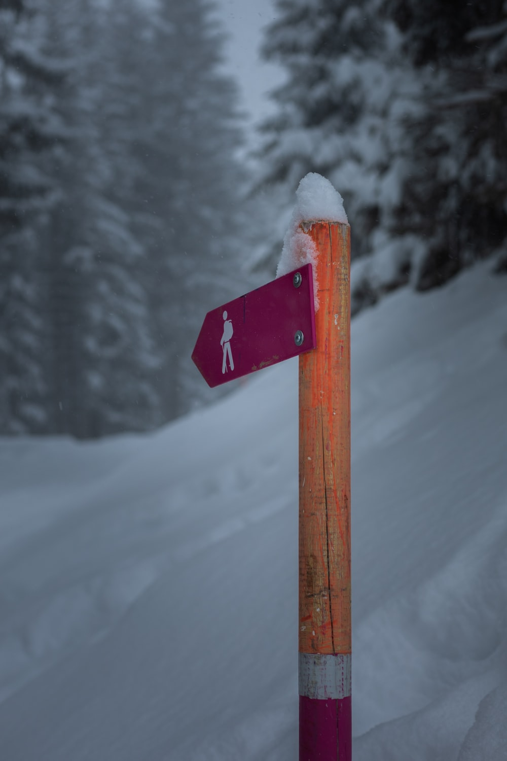 red and white wooden arrow sign on snow covered ground