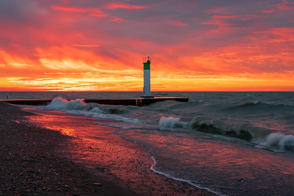 white and black lighthouse on seashore during sunset