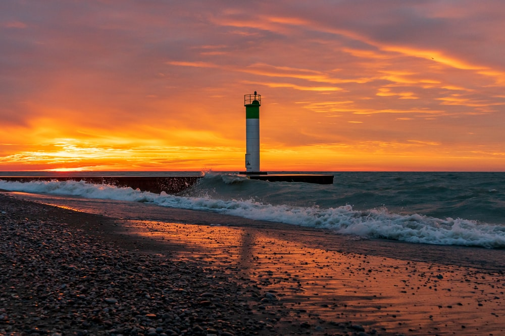 white and black lighthouse on beach during sunset