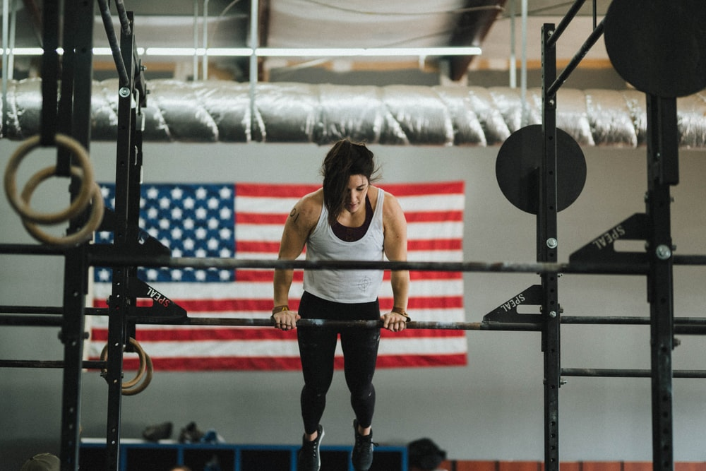 woman in gray tank top and black pants standing on red and black exercise equipment