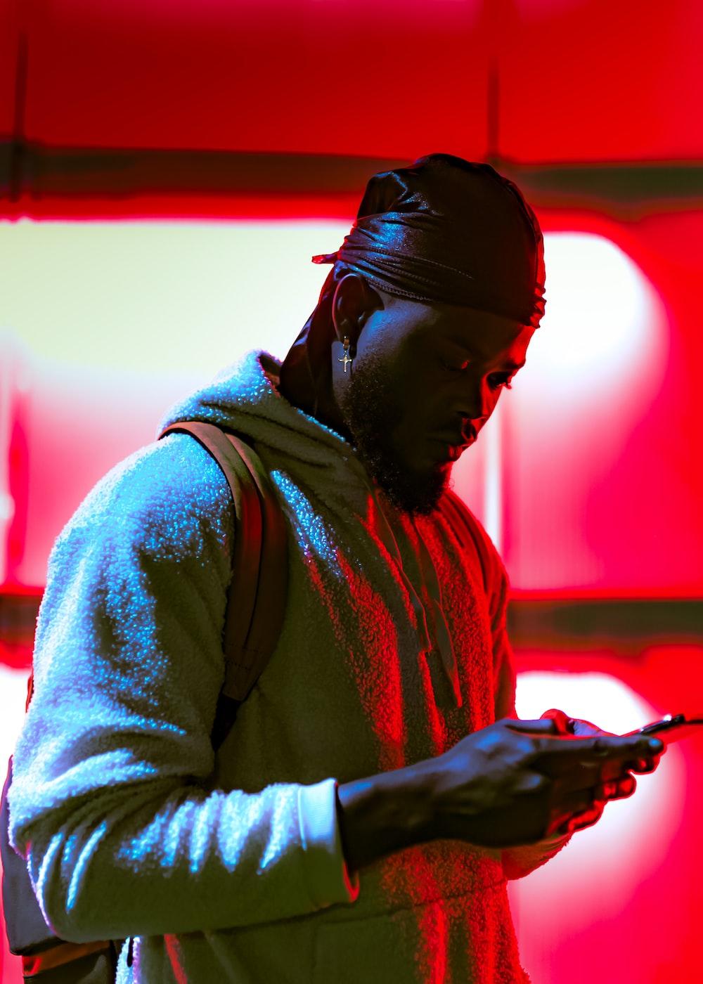 man in gray hoodie holding black smartphone