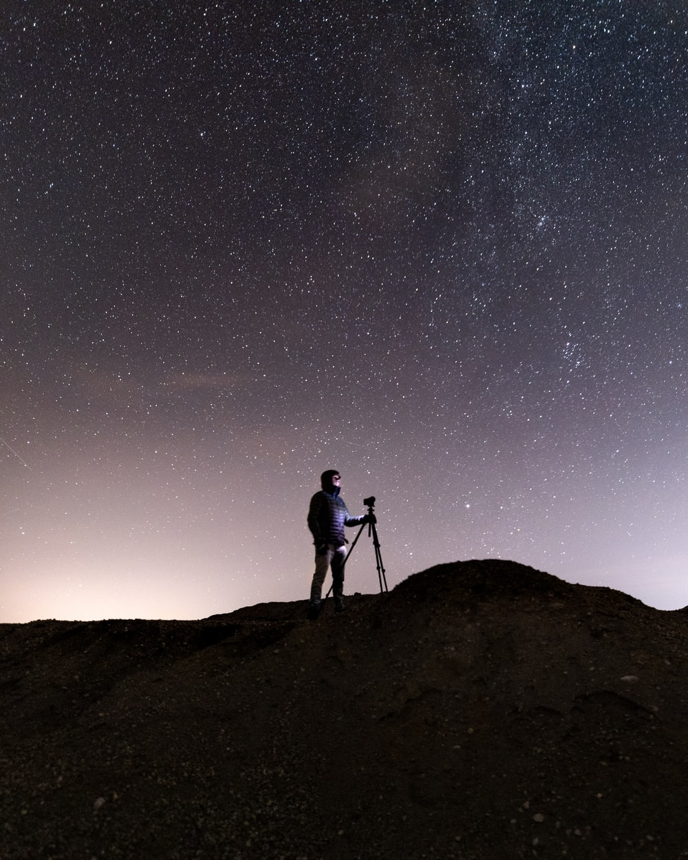 silhouette of man and woman standing on hill under starry night