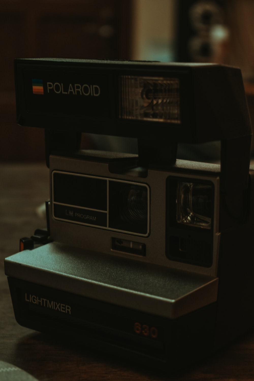black polaroid instant camera on brown wooden table