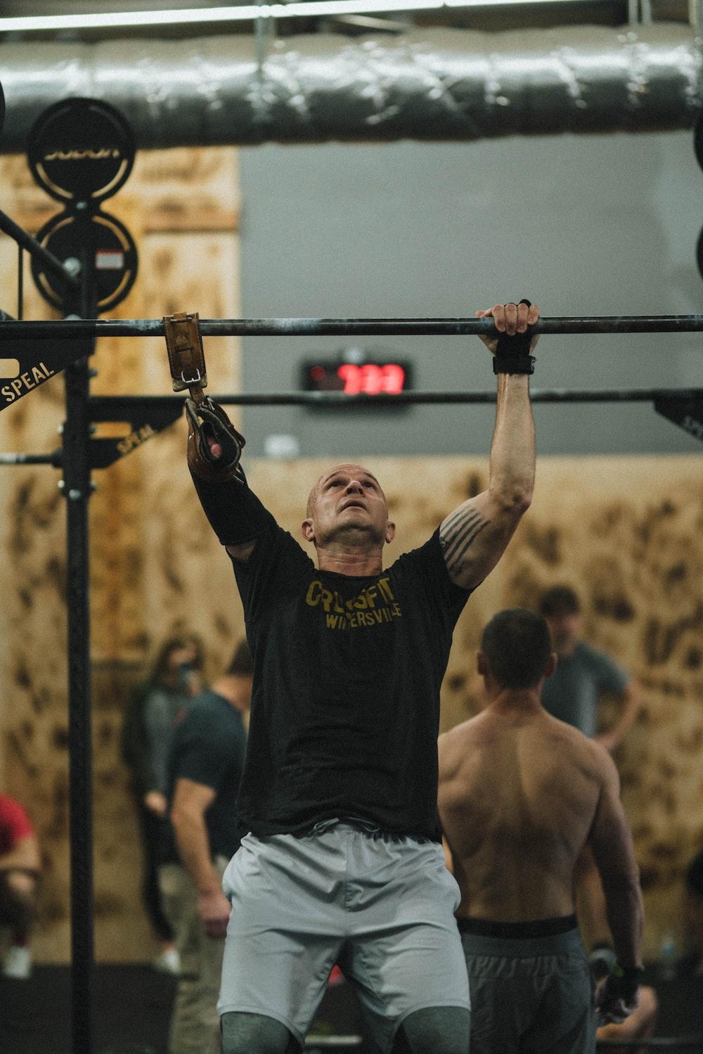 man in black crew neck t-shirt and gray shorts holding black metal bar