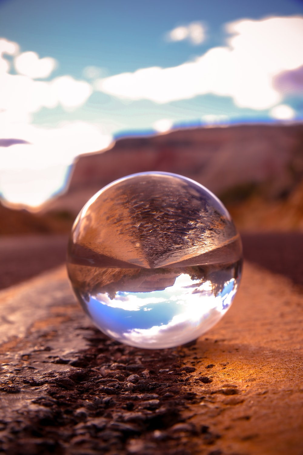 clear glass ball on brown sand during daytime