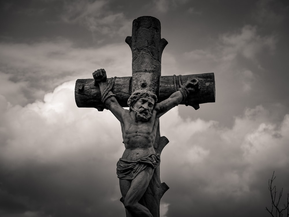 grayscale photo of man holding cross statue