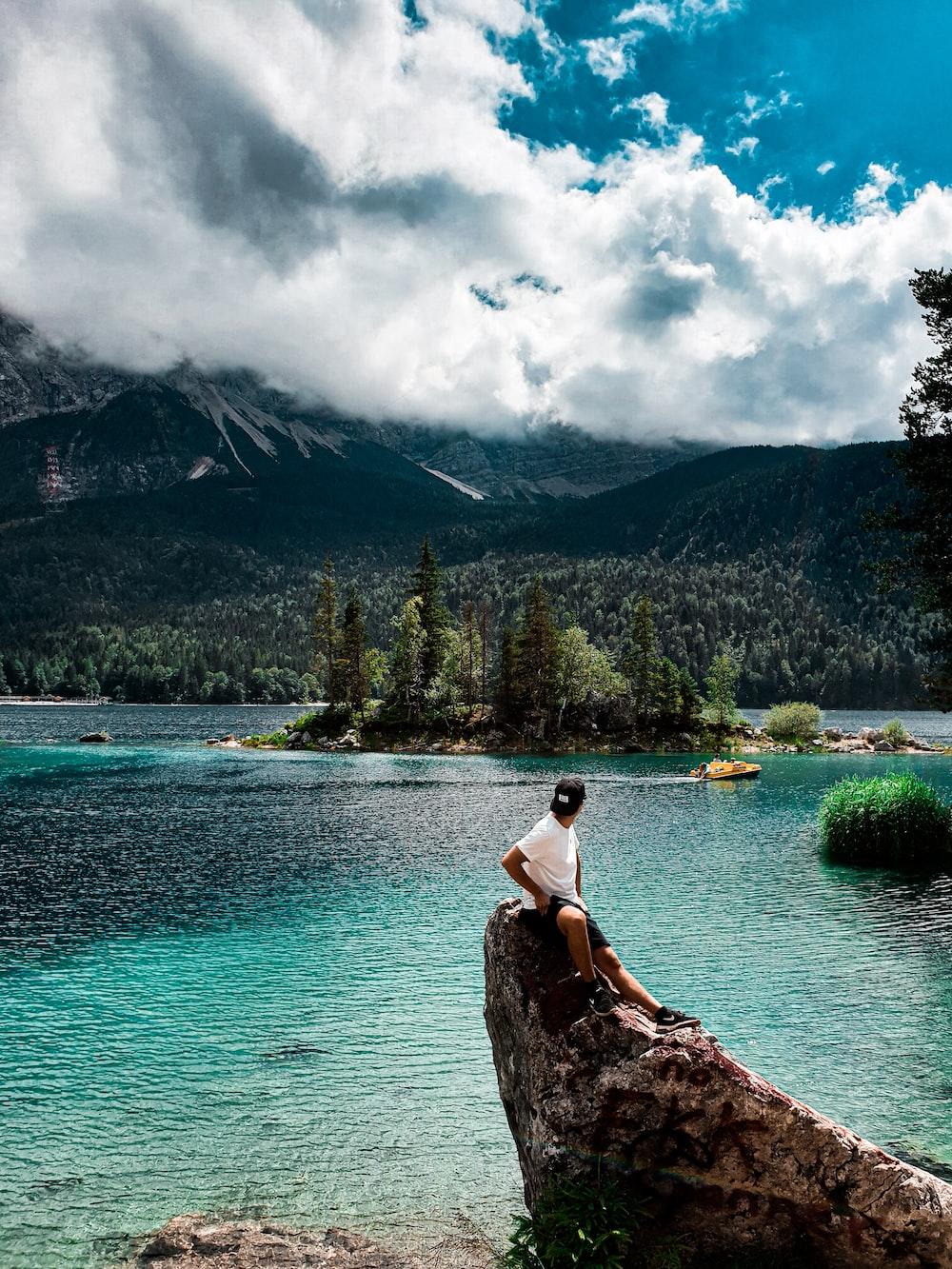 woman in white tank top sitting on rock near lake during daytime