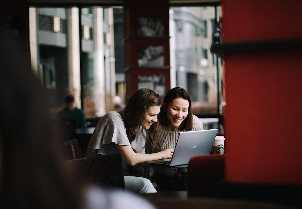 woman in white shirt using macbook