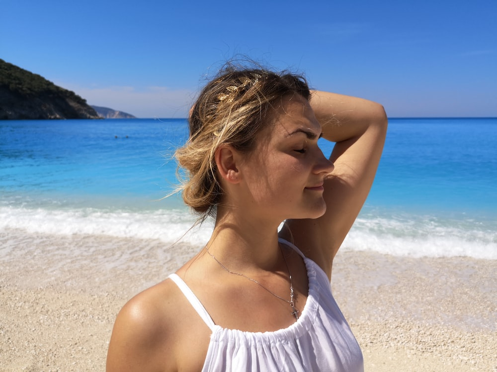 woman in white tank top standing on beach during daytime