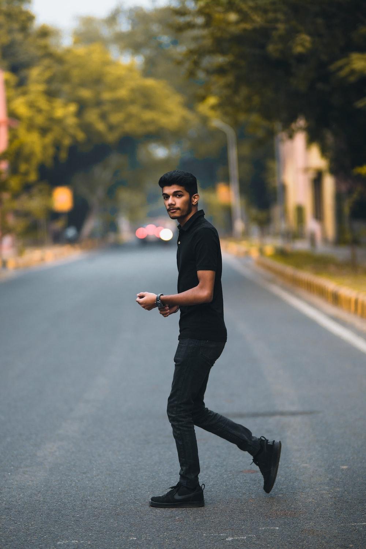 man in black shirt and black pants walking on road during daytime