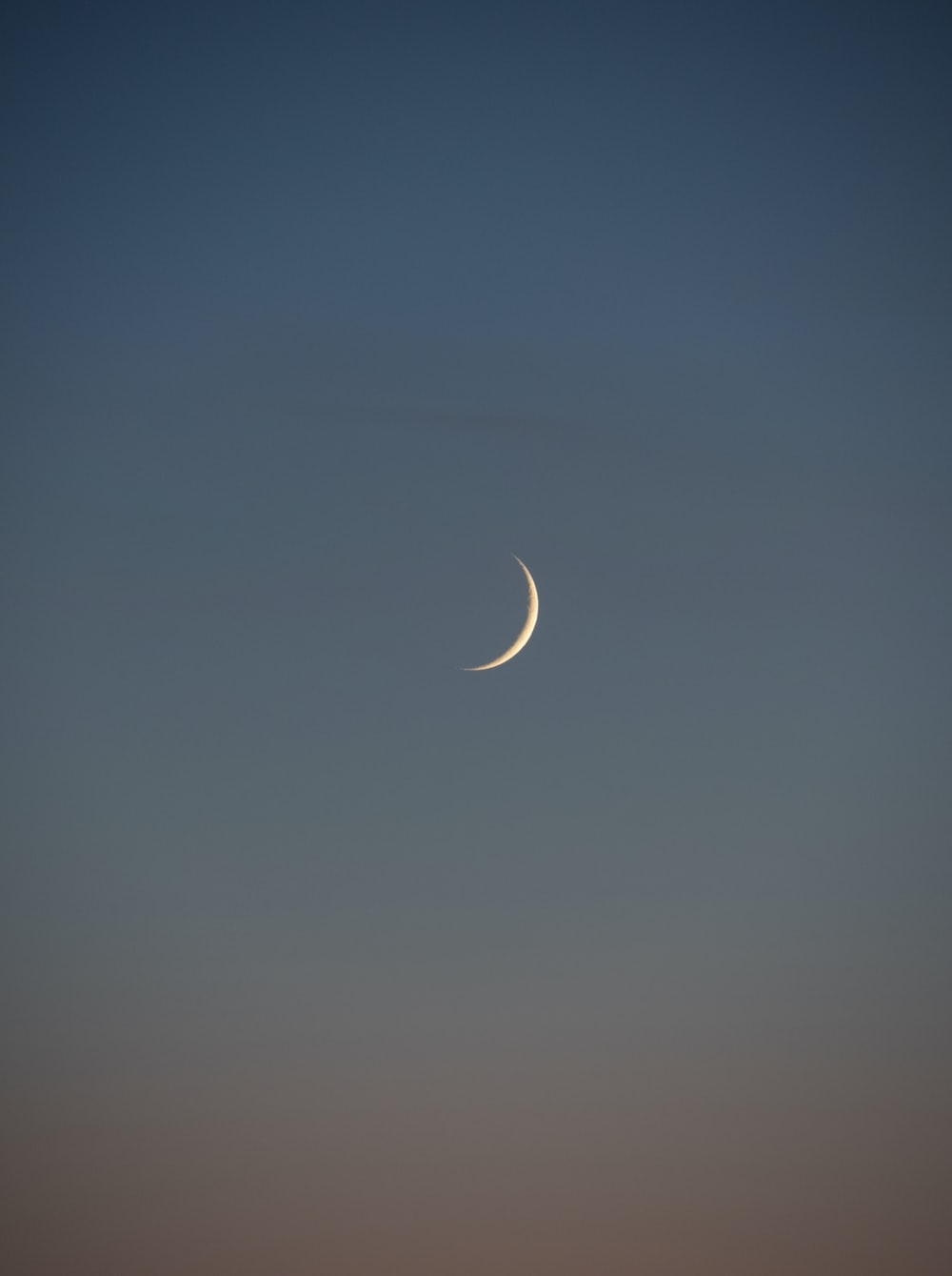 white crescent moon in the sky