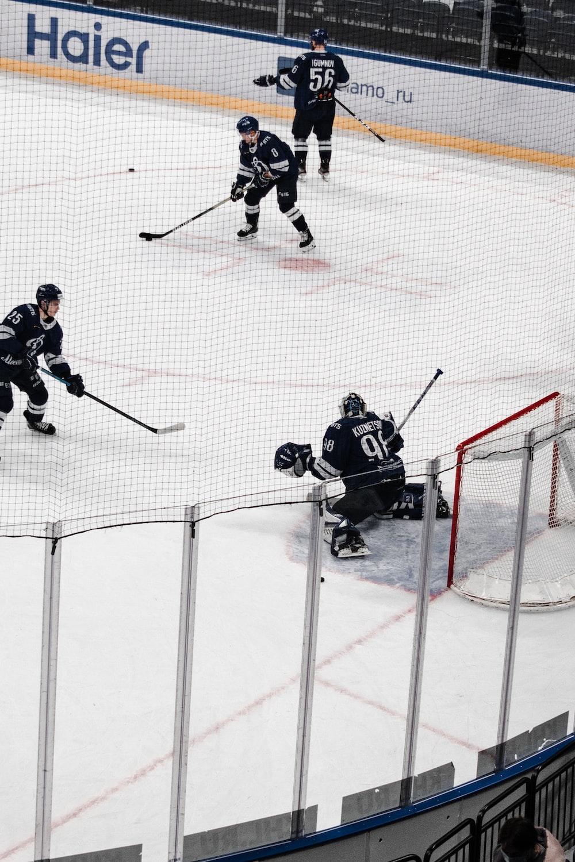 man in black ice hockey jersey playing ice hockey