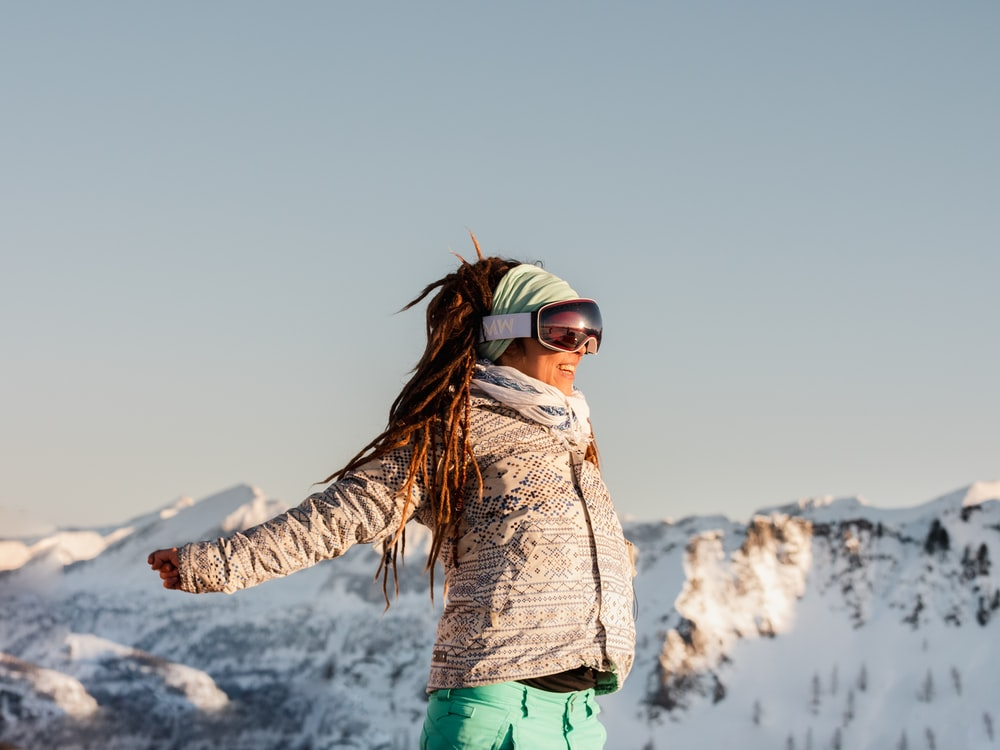 woman in brown jacket and green pants standing on snow covered ground during daytime
