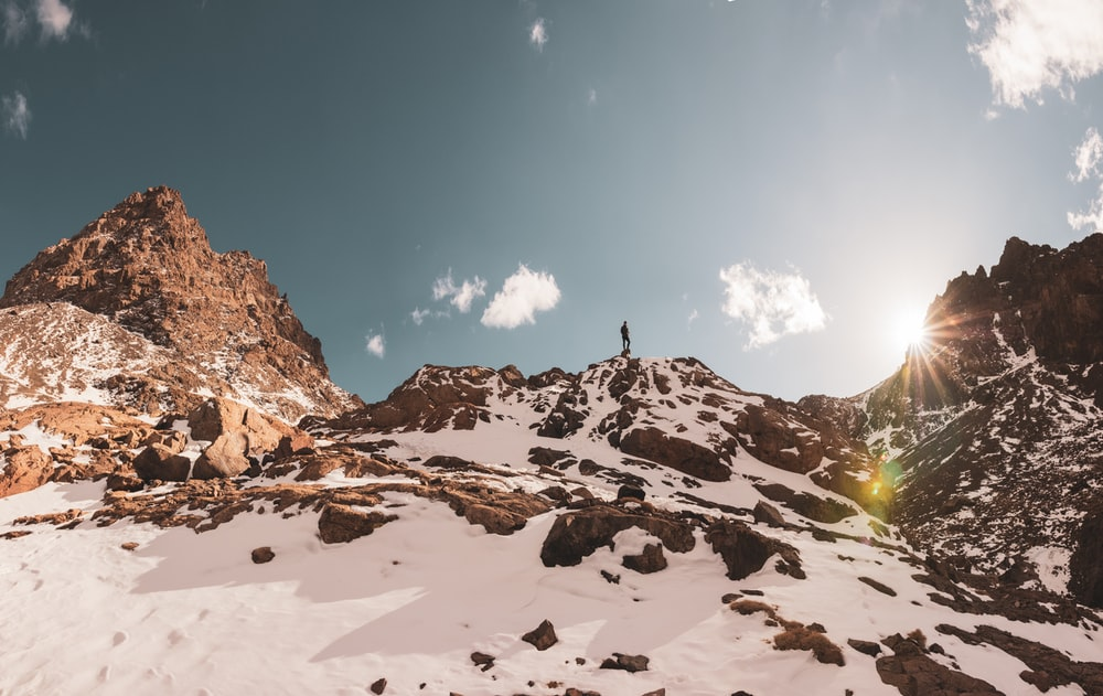 person standing on snow covered mountain during daytime