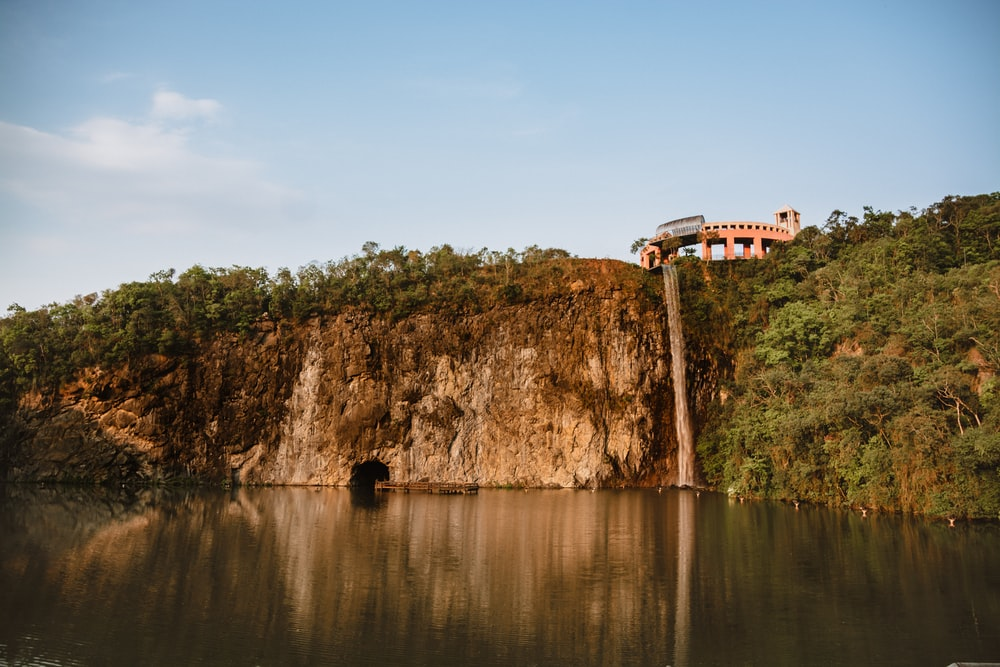 white and red house on brown rock formation beside body of water during daytime
