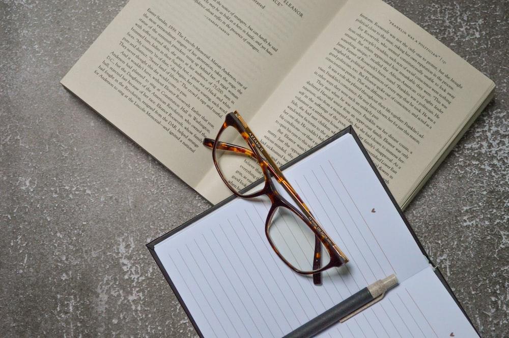 brown framed eyeglasses on white printer paper