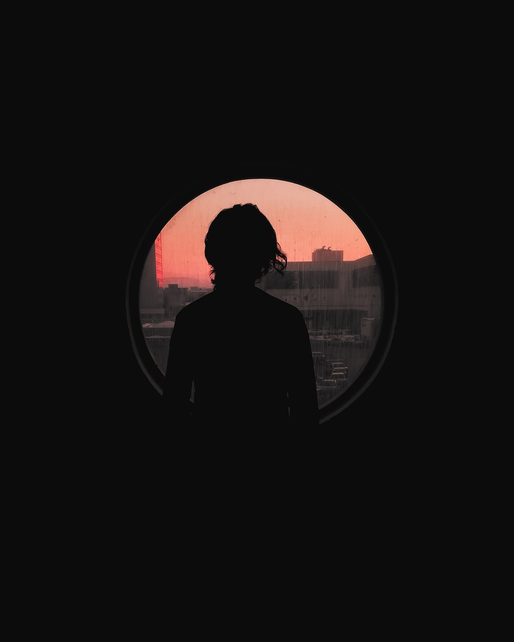 silhouette of man standing near window during daytime