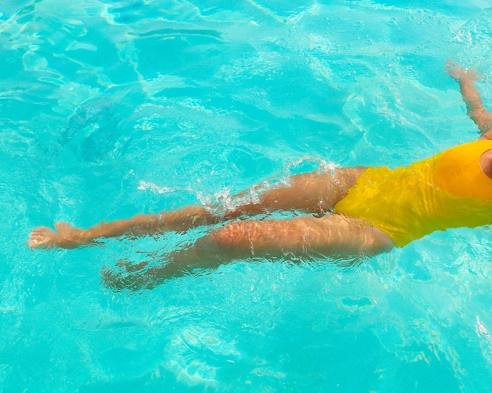 woman in yellow bikini swimming in pool