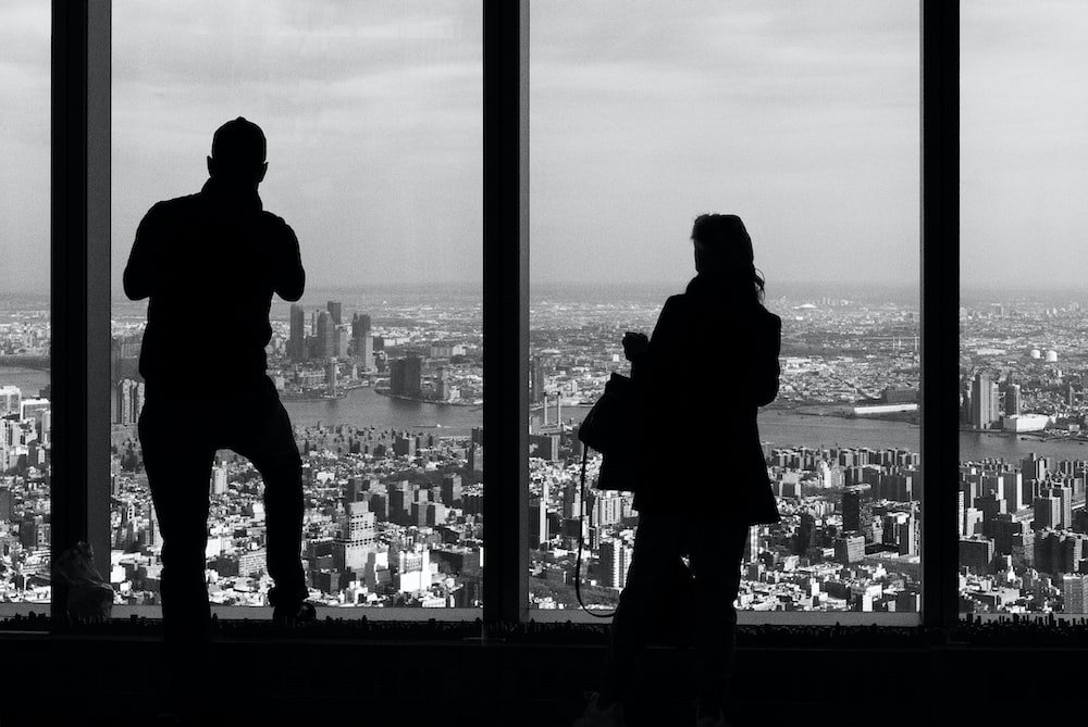 silhouette of man and woman standing on building during night time