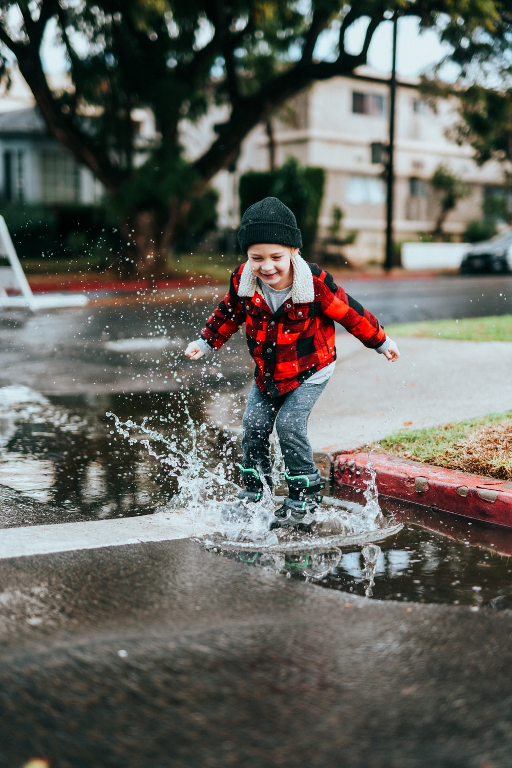 boy in red and black jacket and black knit cap running on wet road during daytime