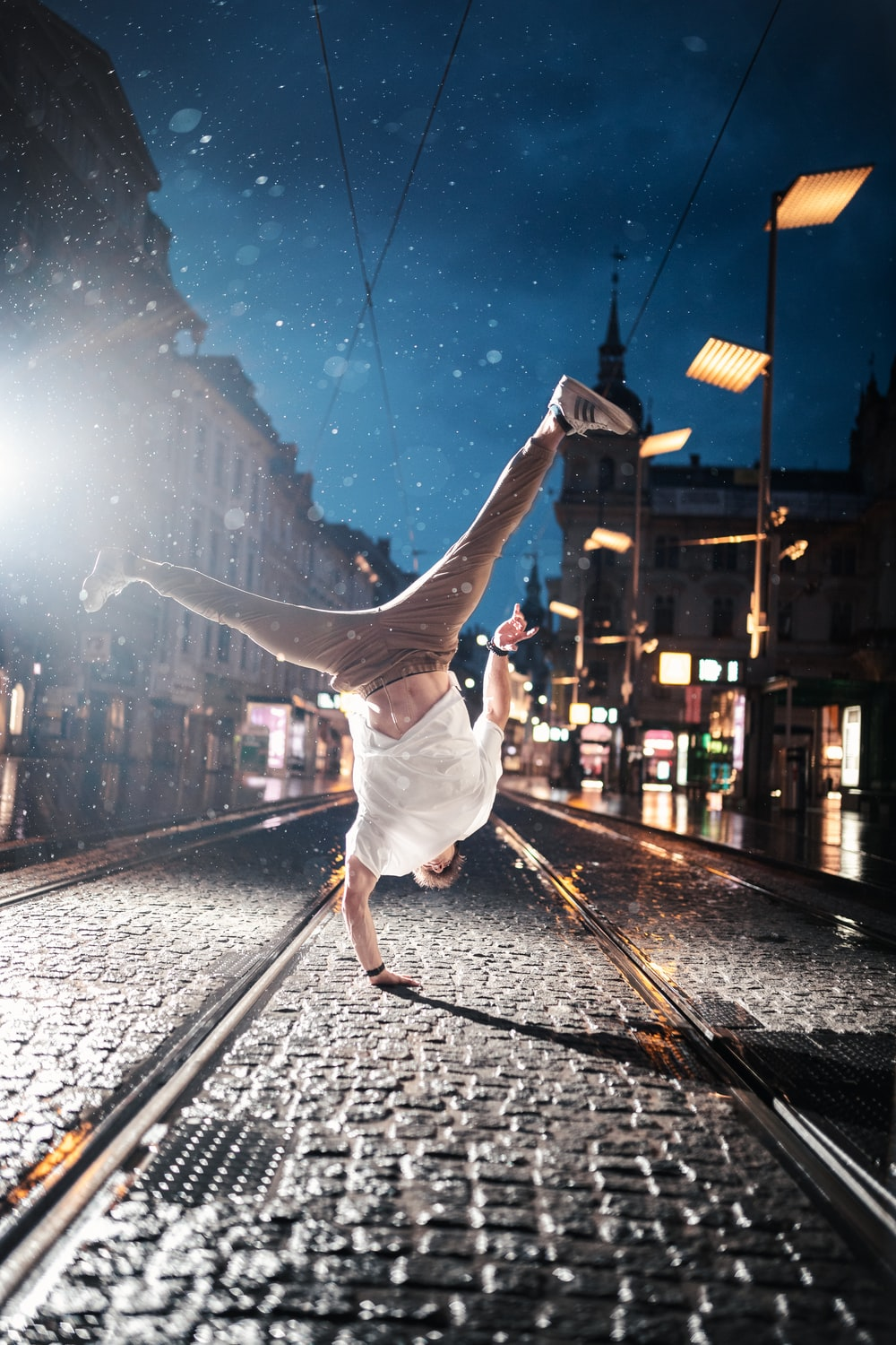 woman in white dress jumping on train rail during night time