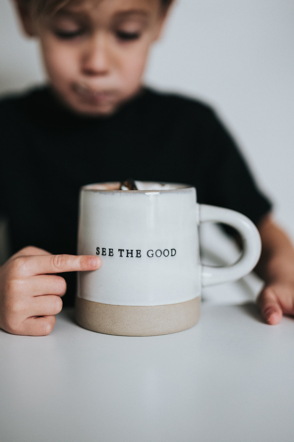 man in black long sleeve shirt holding white ceramic mug