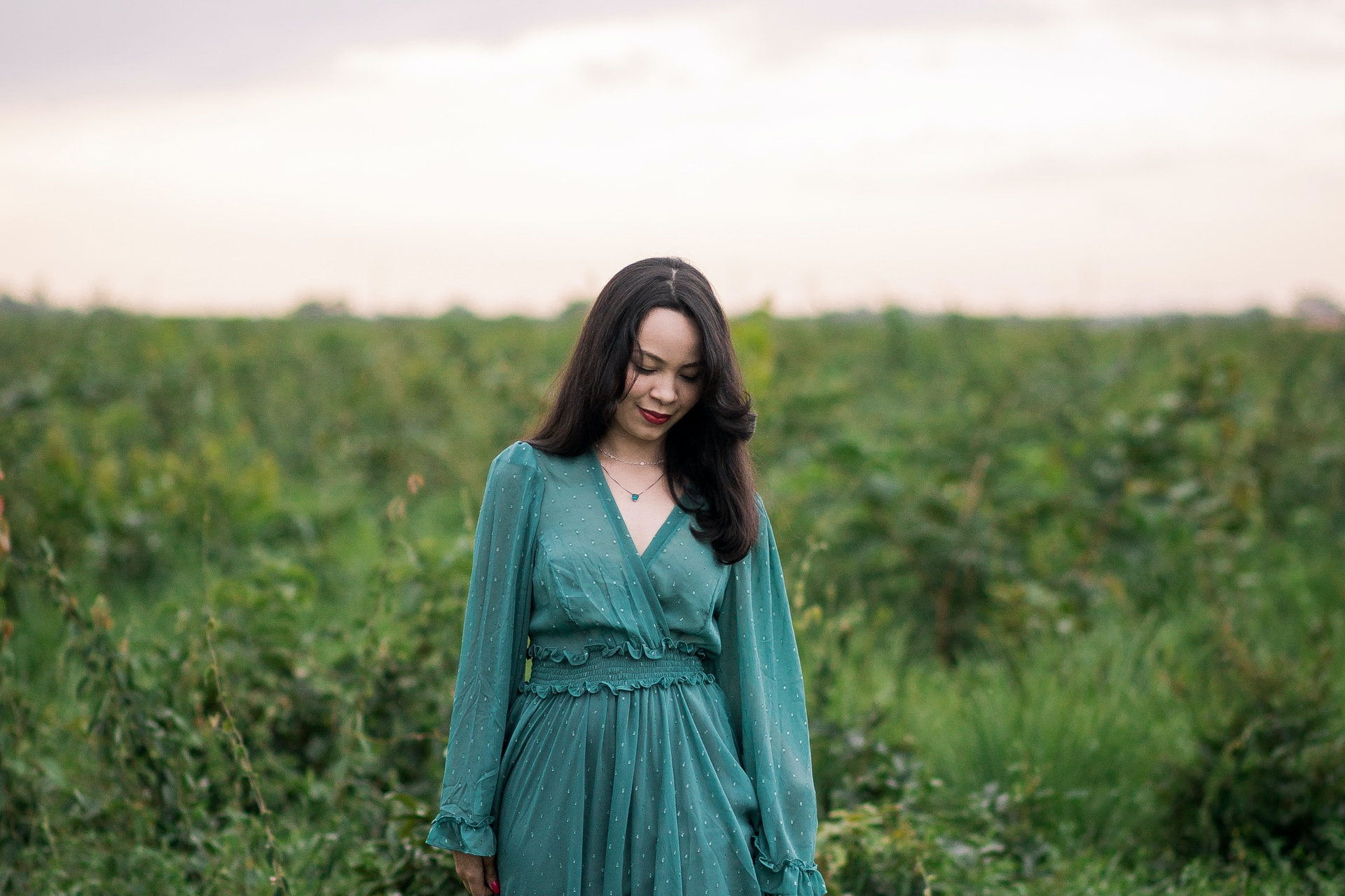 woman in green long sleeve dress standing on green grass field during daytime