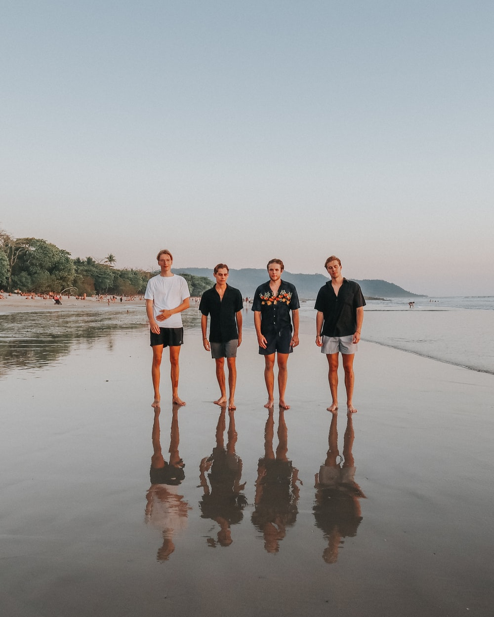 3 women and 2 men standing on beach during daytime