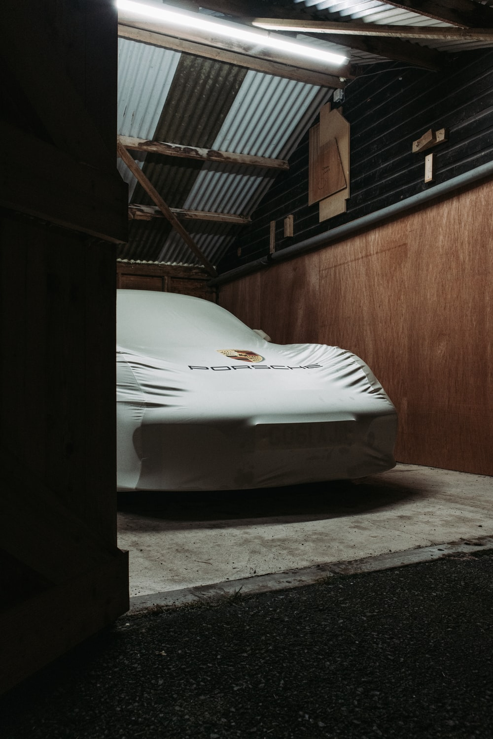 white car parked beside brown wooden wall