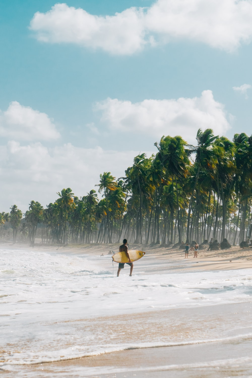 person in yellow shirt carrying brown surfboard walking on beach during daytime