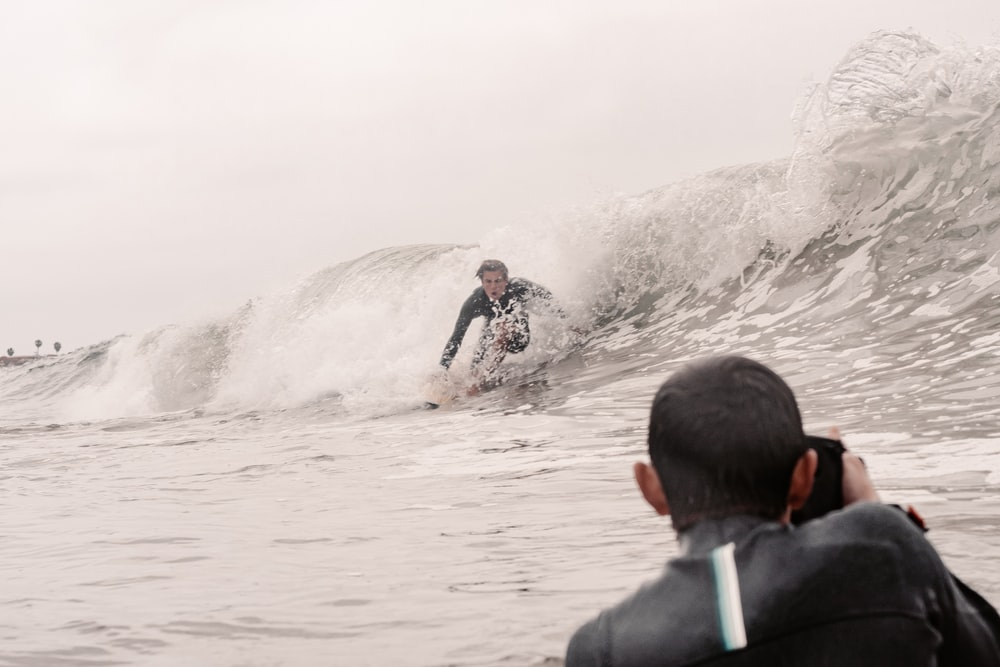 man in black and green jacket surfing on sea waves during daytime