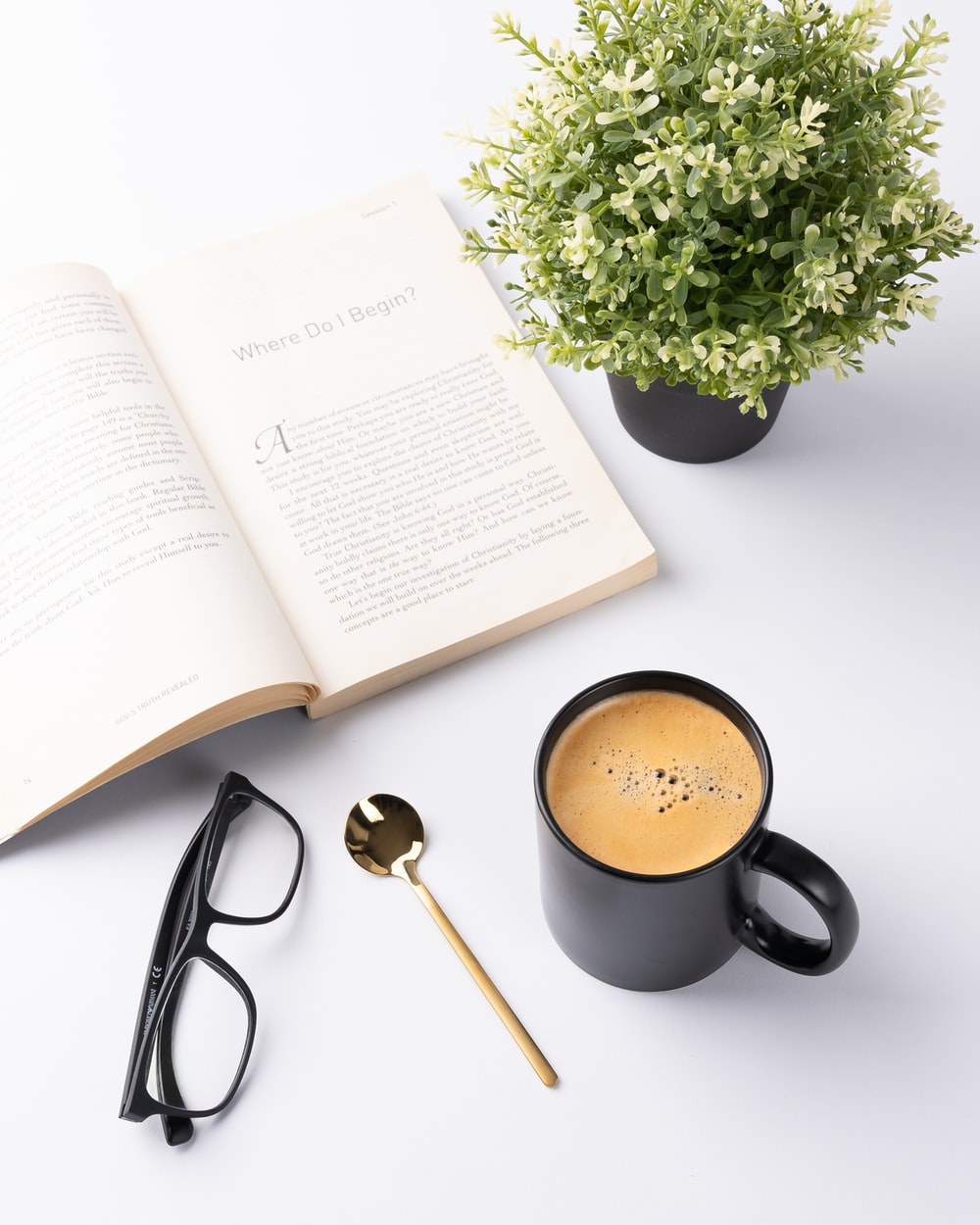 black ceramic mug beside white book page