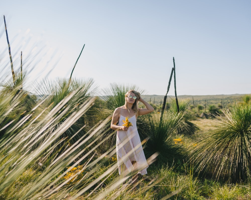 woman in white dress standing on green grass field during daytime