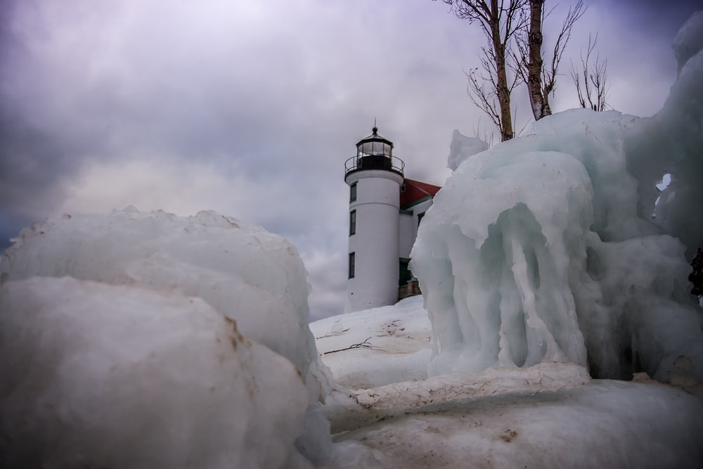 white and black lighthouse covered by snow during daytime