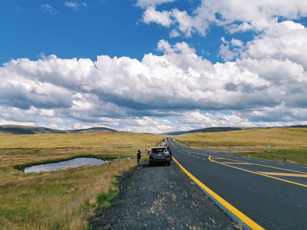 black car on road under white clouds and blue sky during daytime