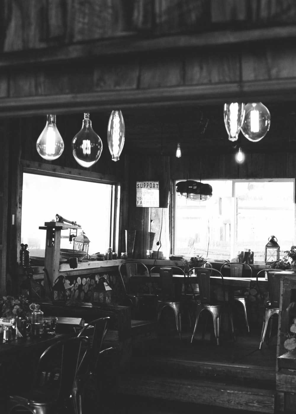 grayscale photo of empty chairs and tables